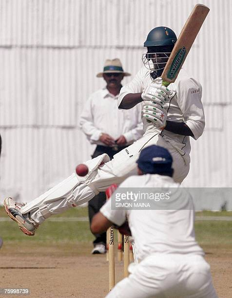 Kenya's batsman Peter Ongondo hits a delivery against India's bowler Irfan Pathan as India's wicket keeper Parthiv Ppatel misses the catch 07 August...