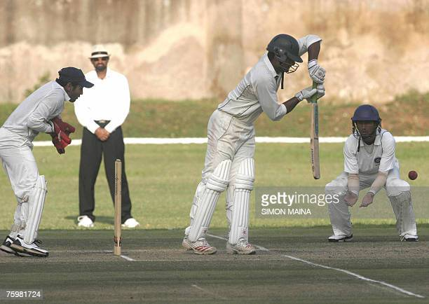 Kenya's batsman Rajesh Budhia hits a delivery as India's fielder Cheteshwar Pujara and wicket keeper Parthiv Patel waits for a catch 06 August 2007...