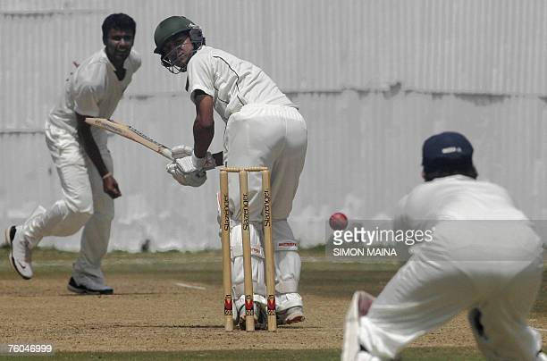 Kenya's batsman Tanmay Mishra looks at India A team wicketkeeper Mahesh Rawat 10 August 2007 as bowler Yo Mahesh looks on during their threeday match...
