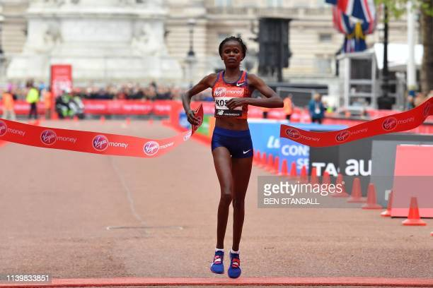 Kenya's Brigid Kosgei crosses the finish line to win the elite women's race of the 2019 London Marathon in central London on April 28 2019 /...