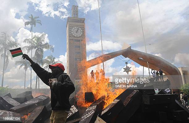 A Kenya's civil activist holds a flag of Kenya as coffins burn outside the parliament in Nairobi on January 16 during a State Burial for the members...