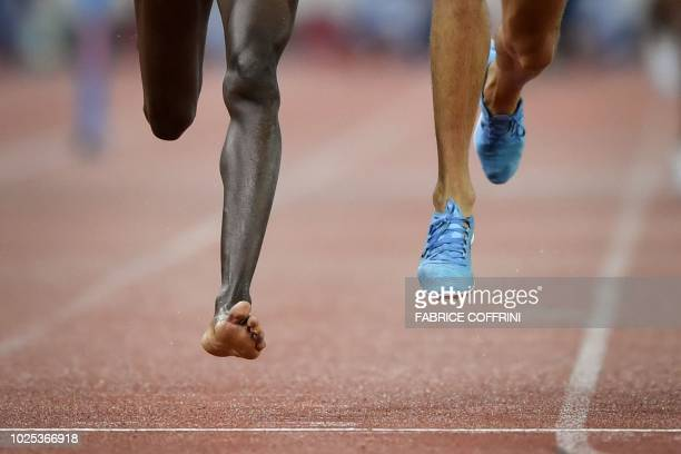Kenya's Conseslus Kipruto , who lost his shoe during the race, wins the men's 3000 meters steeplechase, ahead of second placed Morocco's Soufiane El...