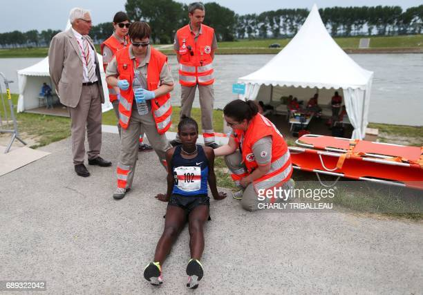 Kenya's contestant Medina Deme sits on the ground next to Red Cross rescuers in the Mont Saint-Michel's marathon on May 28, 2017 near the Mont...