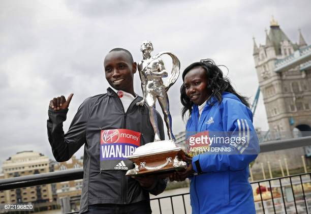 Kenya's Daniel Wanjiru and Mary Keitany pose with the trophy during a photocall beside Tower Bridge the day after winning the men's and women's elite...