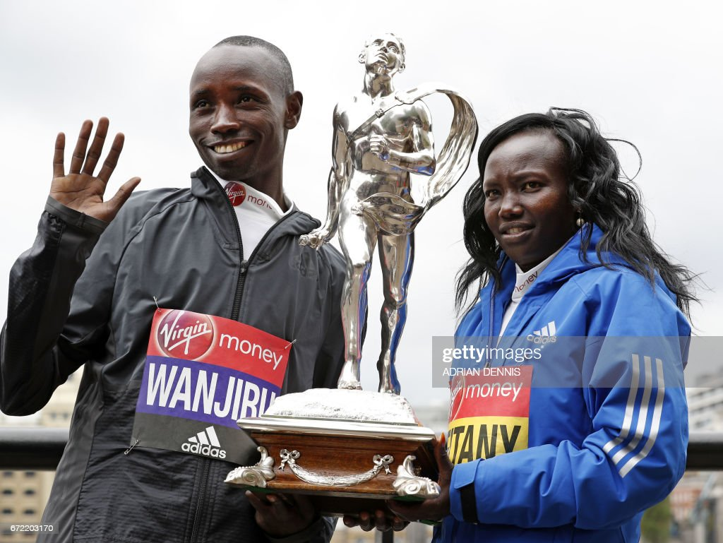 Kenya's Daniel Wanjiru (L) and Mary Keitany pose with the trophy during a photocall beside Tower Bridge, the day after winning the men's and women's elite races at the London Marathon, in London on April 24, 2017. Keitany won a third London Marathon in a time of 2hrs 17min 01sec -- the fastest time in a women-only marathon. /