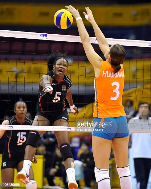 Kenya's Diana Khisa spikes the ball against Francien Huurman of the Netherlands during their first round match of the world women's volleyball...