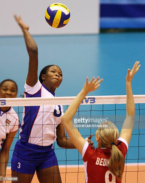 Kenya's Diana Khisa spikes the ball as Poland's Agnieszka Bednarek jumps to block during their FIVB Women's World Cup second round match in Sendai 07...