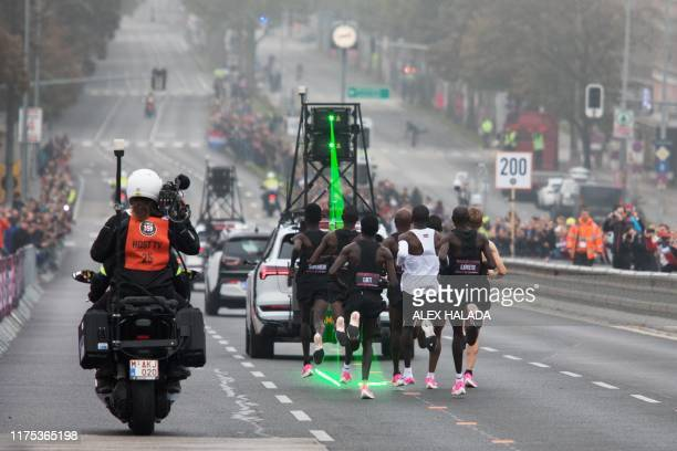 Kenya's Eliud Kipchoge , accompanied by pacemakers and a car in front of them setting the pace with laser beams, takes the start of his attempt to...