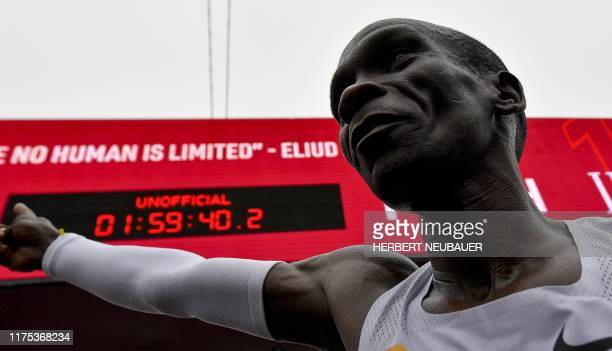 Kenya's Eliud Kipchoge celebrates after crossing the finish line at the end of his attempt to bust the mythical two-hour barrier for the marathon on...