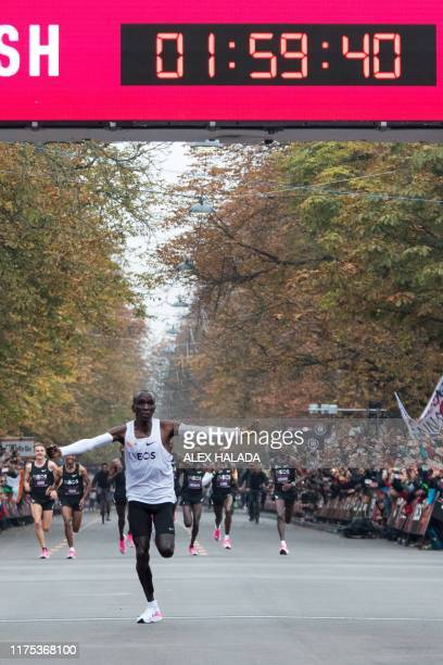 Kenya's Eliud Kipchoge celebrates as he crosses the finish line at the end of his attempt to bust the mythical twohour barrier for the marathon on...