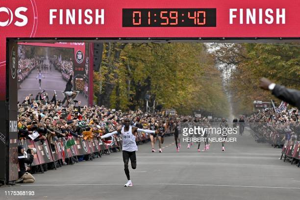 Kenya's Eliud Kipchoge celebrates as he crosses the finish line at the end of his attempt to bust the mythical two-hour barrier for the marathon on...
