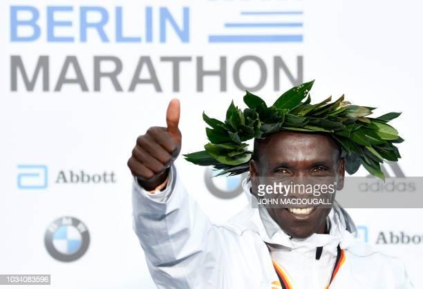 TOPSHOT Kenya's Eliud Kipchoge celebrates on the podium during the winner's ceremony after winning the Berlin Marathon setting a new world record on...
