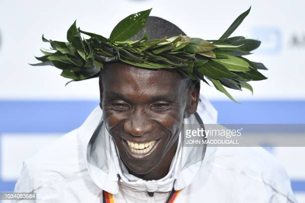 Kenya's Eliud Kipchoge celebrates on the podium with a wreath of laurel during the winner's ceremony after winning the Berlin Marathon setting a new...