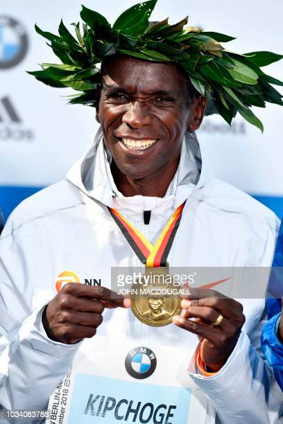 Kenya's Eliud Kipchoge celebrates on the podium with his medal during the winner's ceremony after winning the Berlin Marathon setting a new world...