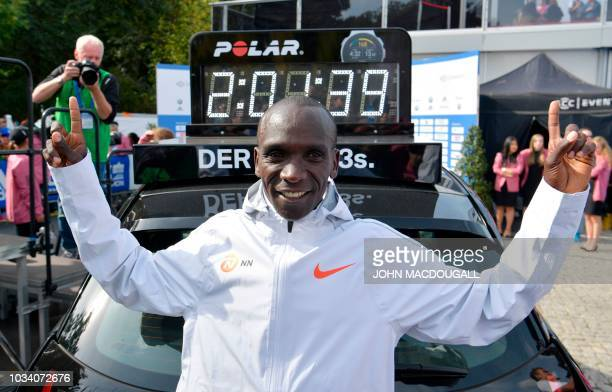 Kenya's Eliud Kipchoge stands in front of a clock displaying his time after winning the Berlin Marathon setting a new world record with 2h01m39s on...