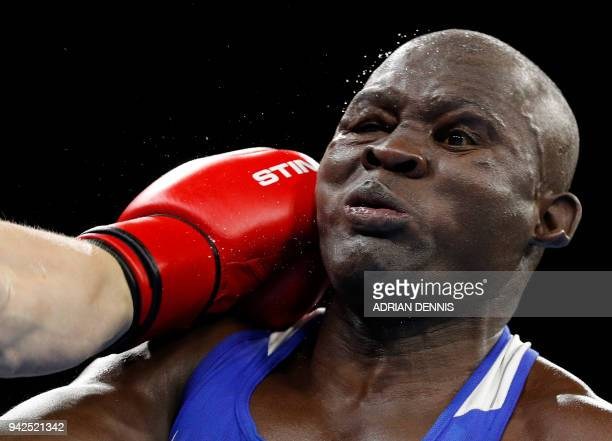 TOPSHOT Kenya's Elly Ochola gets punched by Scotland's Scott Forrest during the mens heavy category preliminary boxing match during the 2018 Gold...