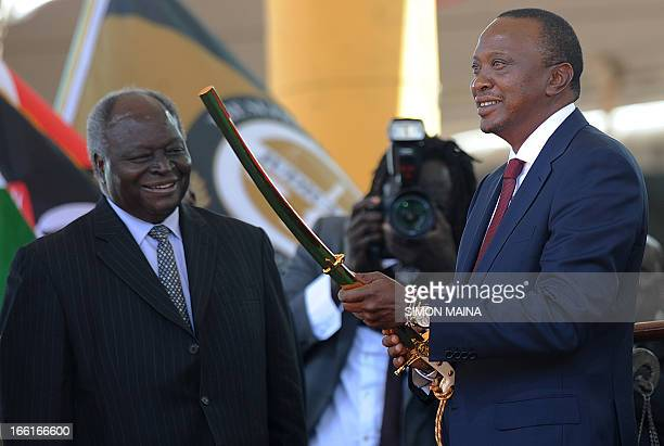 Kenya's fourth president Uhuru Kenyatta receives a sword as a symbol of authority from former president Mwai Kibaki during his inauguration at the...
