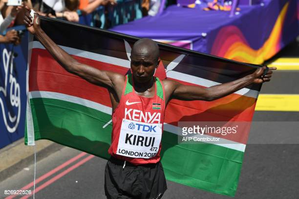 Kenya's Geoffrey Kipkorir Kirui poses with his national flag after winning the men's marathon athletics event at the 2017 IAAF World Championships in...