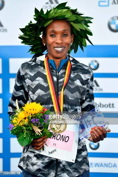 Kenya's Gladys Cherono poses on the podium with her medal and her trophy during the winner's ceremony of the women's category of the Berlin Marathon...