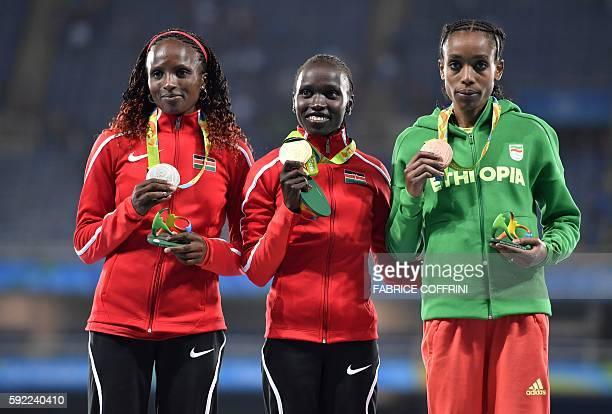 Kenya's Hellen Onsando Obiri Kenya's Vivian Jepkemoi Cheruiyot and Ethiopia's Almaz Ayana pose during the podium ceremony for the Women's 5000m...
