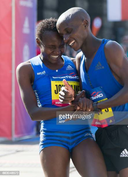 Kenya's Joyciline Jepkosgei celebrates her victory with an unidentified competitor after winning the International Half Marathon on April 1 2017 in...