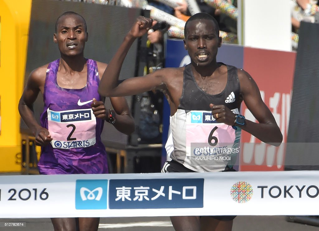 Kenya's Kiprop Kipyego (R) reacts as he crosses the finish line ahead of compatriot Dickson Chumba (L) during the men's category of the Tokyo Marathon in Tokyo on February 28, 2016.