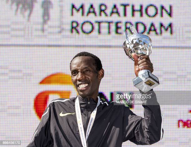 Kenya's Marius Kimutai poses on the podium with his trophy after winning the men's race of the 37nd edition of the Rotterdam Marathon in Rotterdam on...