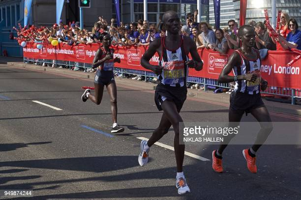 Kenya's Mary Keitany accompanied by male pacemakers runs during the 2018 London Marathon in central London on April 22 2018