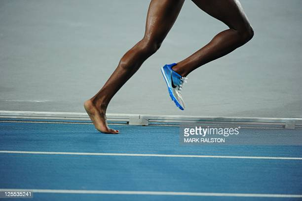 Kenya's Mercy Wanjiku Njoroge runs with only one shoe after the other fell off during the women's 3000 metres steeplechase final at the International...