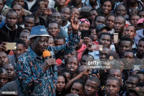 TOPSHOT Kenya's opposition leader Raila Odinga of the opposition National Super Alliance coalition speaks to supporters as he arrives on a car to a...