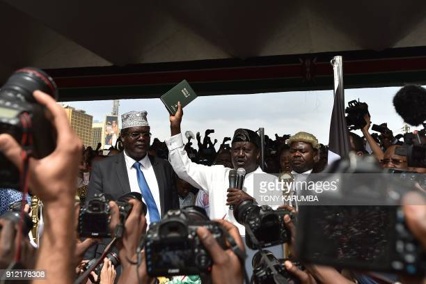 TOPSHOT Kenya's opposition National Super Alliance coalition leader Raila Odinga holds up a bible as he swearsin himself as the 'people's president'...