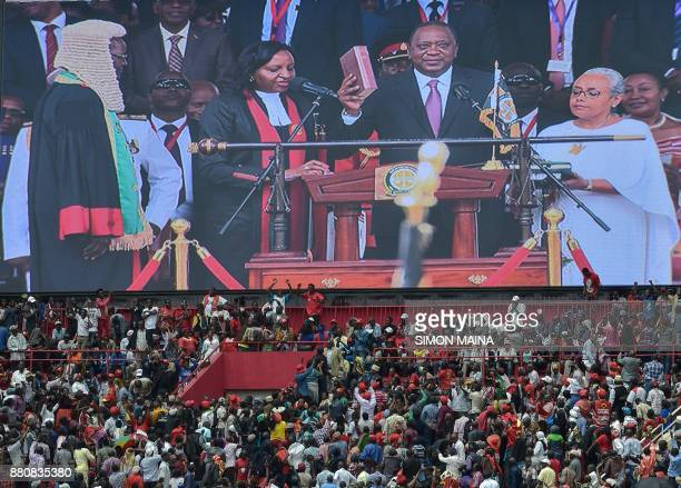 Kenya's President Uhuru Kenyatta appears on a giant screen as he takes oath of office during his inauguration ceremony at Kasarani Stadium on...