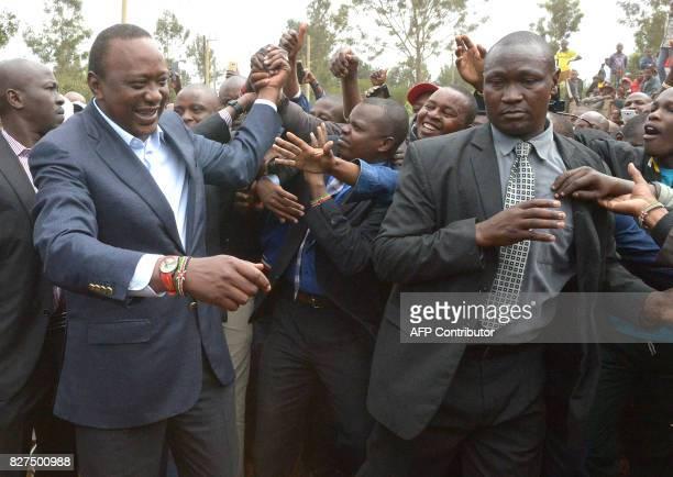 Kenya's President Uhuru Kenyatta greets supporters after voting at a polling station during the August 8 2017 presidential election in Gatundu Kiambu...