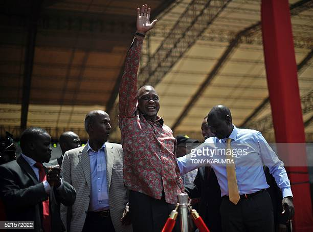 Kenya's President Uhuru Kenyatta hails at the audience as he arrives with his Deputy president William Ruto for an interreligious event at the Afraha...