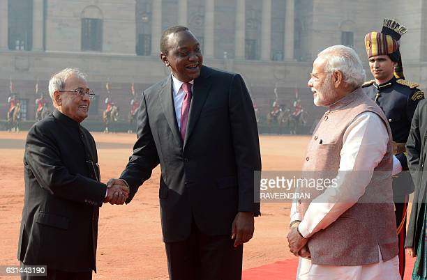 Kenya's President Uhuru Kenyatta shakes hands with India's President Pranab Mukherjee as India's Prime Minister Narendra Modi looks on after a...