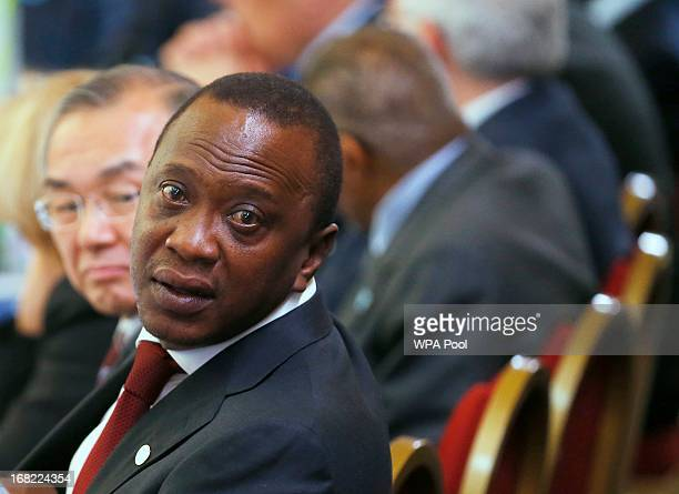 Kenya's President Uhuru Kenyatta turns to speak to a member of his delegation during the Somali conference on May 7 2013 in London England The...