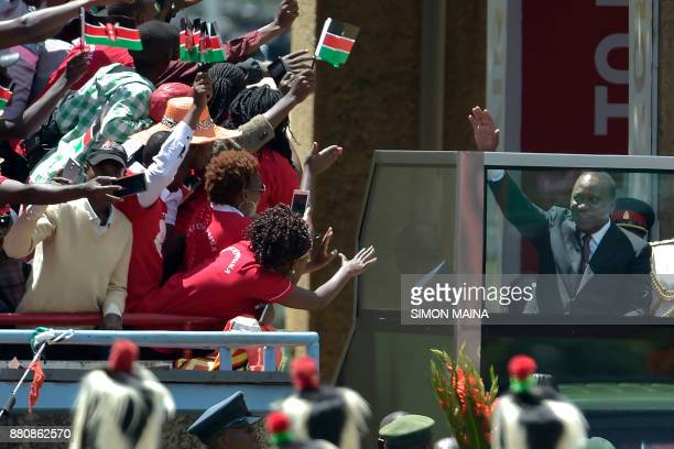 TOPSHOT Kenya's President Uhuru Kenyatta waves to supporters as he arrives to take oath of office during his inauguration ceremony at Kasarani...