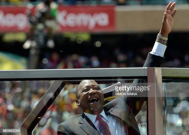 Kenya's President Uhuru Kenyatta waves to supporters upon his arrival to take oath of office during his inauguration ceremony at Kasarani Stadium on...