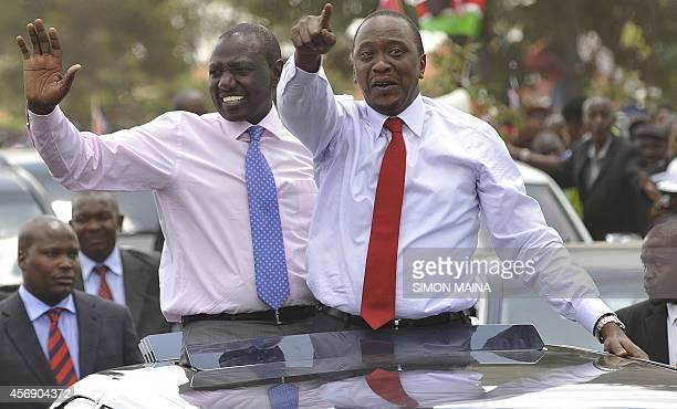 Kenya's president Uhuru Kenyatta waves to the welcoming crowd flanked by deputypresident William Ruto on October 9 2014 in Nairobi a day after...
