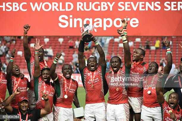 Kenya's team celebrate with the trophy after defeating Fiji in the cup final at the Singapore Sevens rugby tournament on April 17 2016 / AFP / ROSLAN...