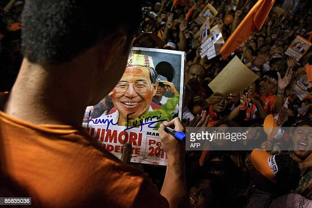 Kenyi Fujimori son of Peru's former President Alberto Fujimori signs an autograph on a poster of his father during a rally in support of him outside...