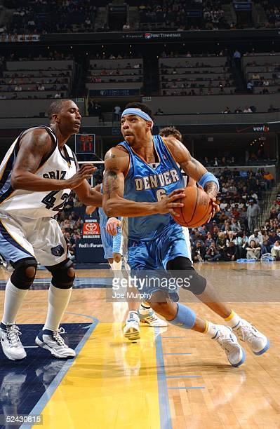 Kenyon Martin of the Denver Nuggets drives around Lorenzen Wright of the Memphis Grizzlies during the game at FedEx Forum on February 25 2005 in...