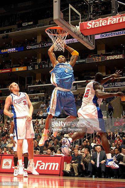 Kenyon Martin of the Denver Nuggets goes up for a dunk between Chris Kaman and Tim Thomas of the Los Angeles Clippers at Staples Center on October 31...