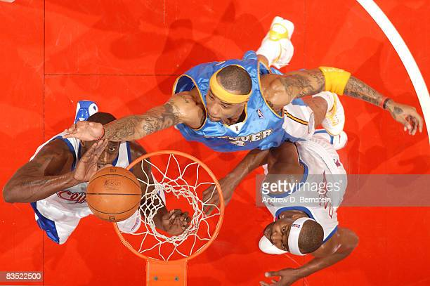 Kenyon Martin of the Denver Nuggets goes up for a shot against Tim Thomas and Baron Davis of the Los Angeles Clippers at Staples Center on October 31...