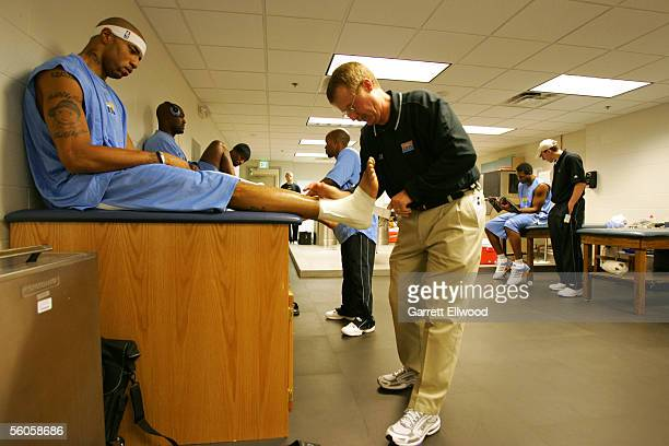 Kenyon Martin of the Denver Nuggets has his ankles taped by team trainer Jim Gillen prior to an open scrimmage October 11 2005 at Clune arena on the...