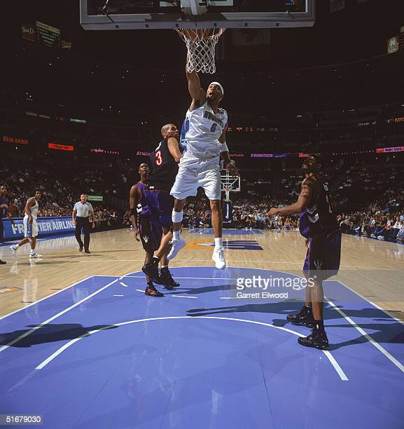 Kenyon Martin of the Denver Nuggets reaches for the basket against Loren Woods of the Toronto Raptors during the game at Pepsi Center on October 26...