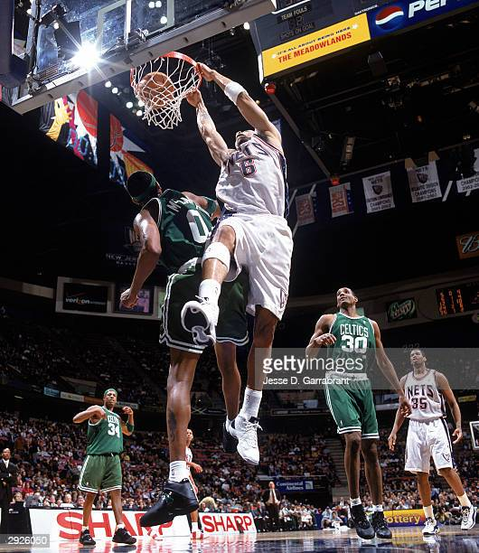 Kenyon Martin of the New Jersey Nets dunks the ball over Walter McCarty of the Boston Celtics during the NBA game at Continental Airlines Arena on...