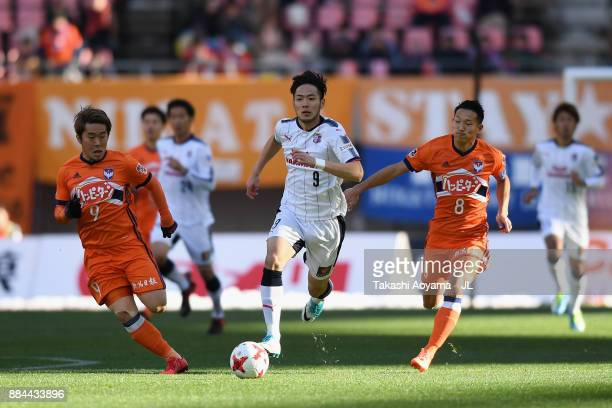 Kenyu Sugimoto of Cerezo Osaka competes for the ball against Ryohei Yamazaki and Kei Koizumi of Albirex Niigata during the JLeague J1 match between...