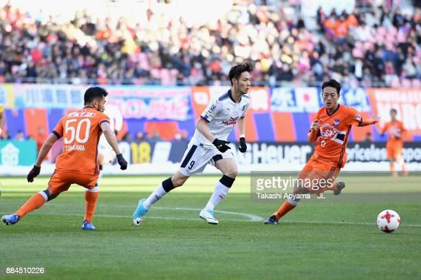 Kenyu Sugimoto of Cerezo Osaka controls the ball under pressure of Seitaro Tomisawa and Ryota Isomura of Albirex Niigata during the JLeague J1 match...