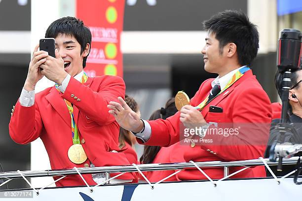 Kenzo Shirai and Koji Yamamuro take pictures on the top of a double decker bus during the Rio Olympic Paralympic 2016 Japanese medalist parade in the...